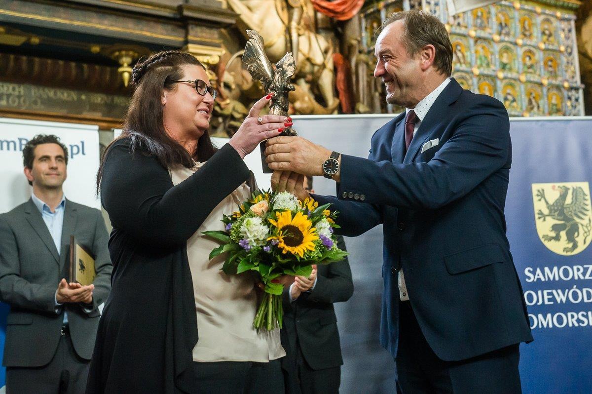 Mieczysław Struk (po prawej) wręcza statuetkę Gryfa Gospodarczego Monice Micał-Połczyńskiej, właścicielce firmy FLEK Import-Export