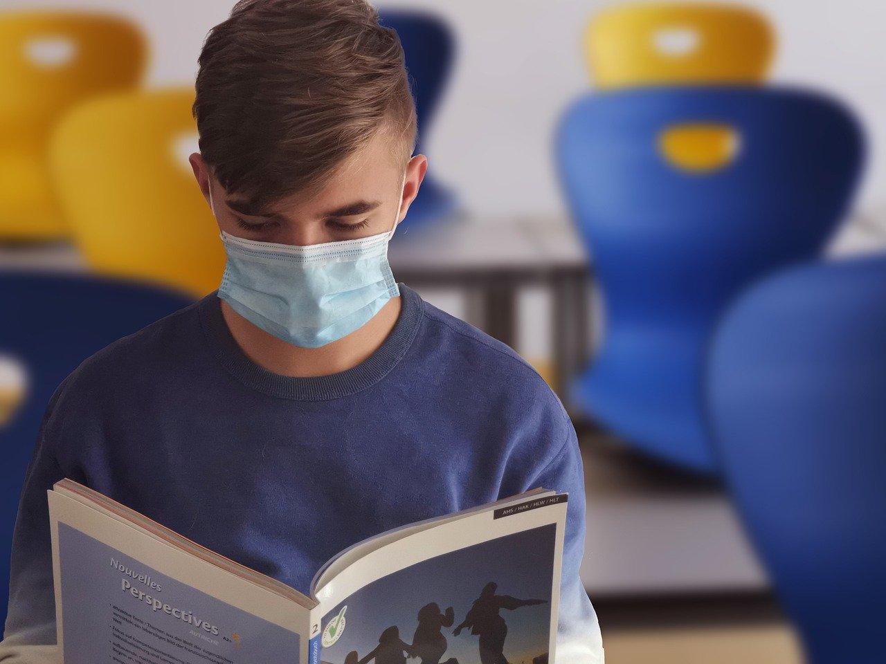 Uczeń w maseczce czyta książke
