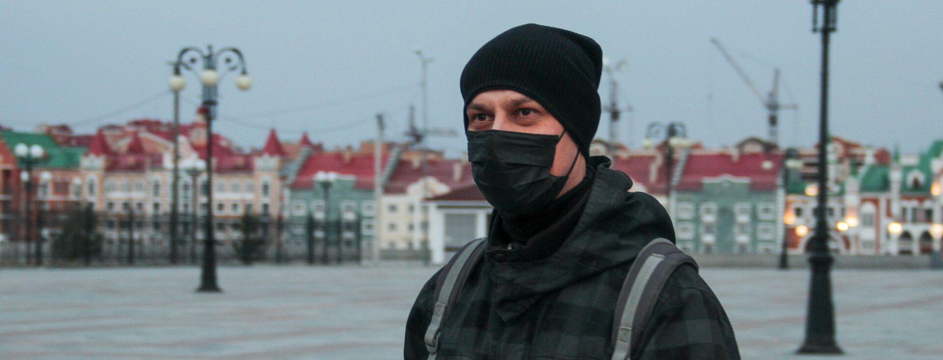 Mężczyzna w czapce i masce na placu