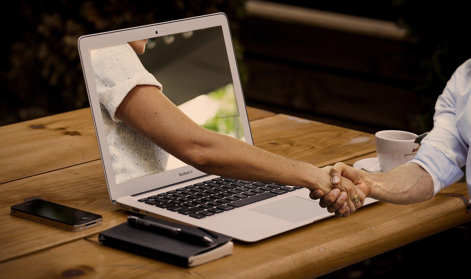 Ręka wychodząca z laptopa ściska rękę osoby siedzącej przy stole