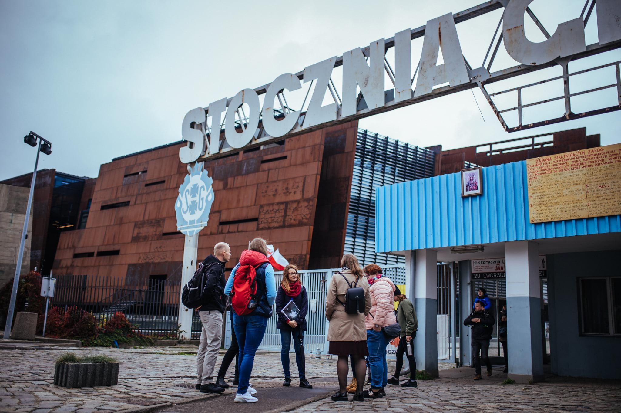 Ludzie stoją przed bramą Stoczni Gdańskiej