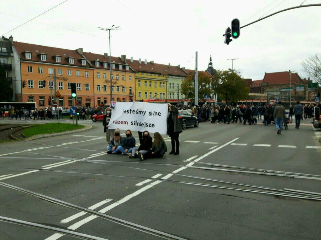 kobiety z banerem siedzą na środku ulicy w centrum gdańska