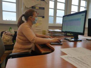Kobieta siedzi przy biurku przed komputerem
