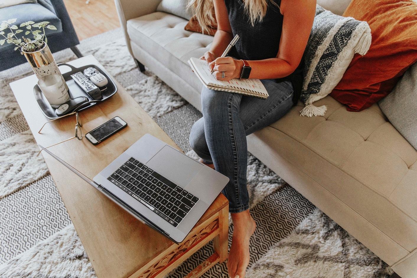 Kobieta robi notatki przed komputerem