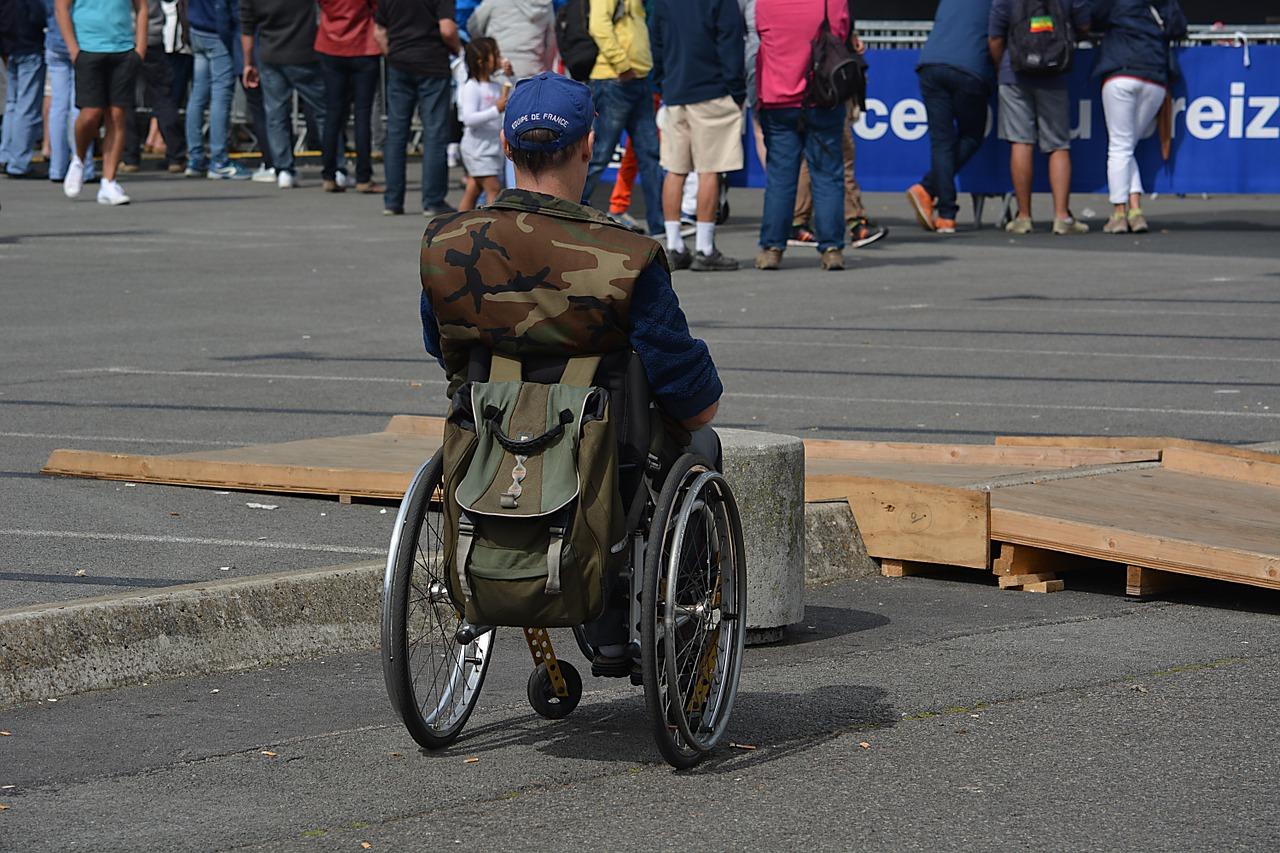 osoba na wózku inwaldzkim stoi tyłem, na drugim planie widać ludzi stojących tyłem