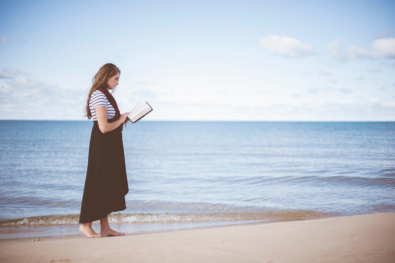 kobieta idzie wzdłuż plaży czytając ksiazkę