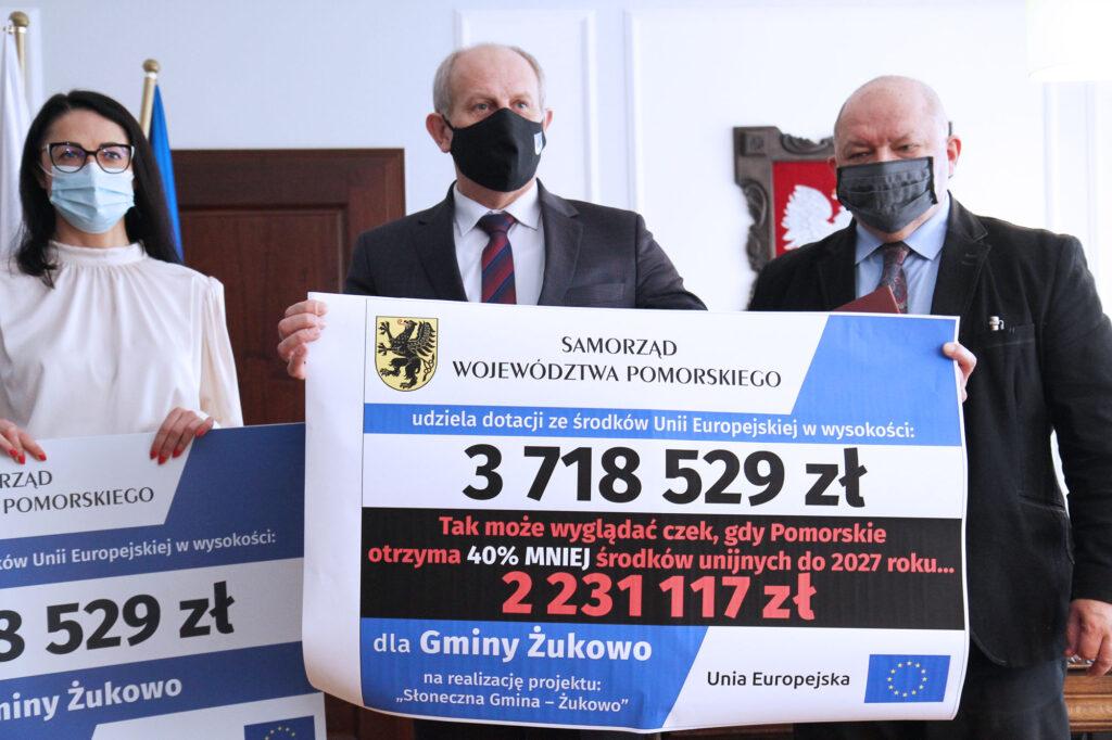 burmistrz żukowa trzyma symboliczny czek ze zmniejszoną kwotą