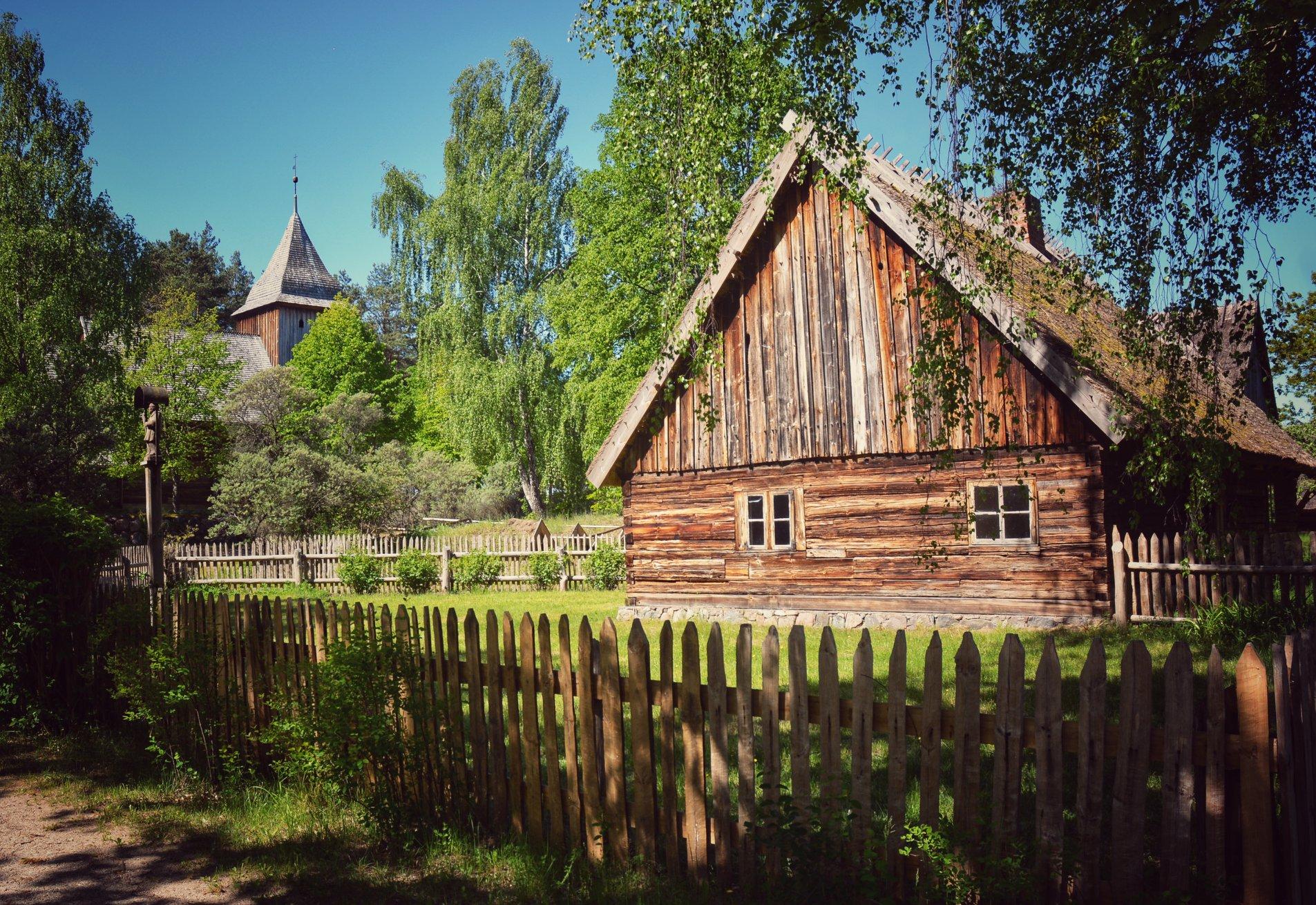 Widok na zabudowę skansenu we Wdzydzach Kiszewskich, Na pierwszym planie drewniana chata, w tle - kościół