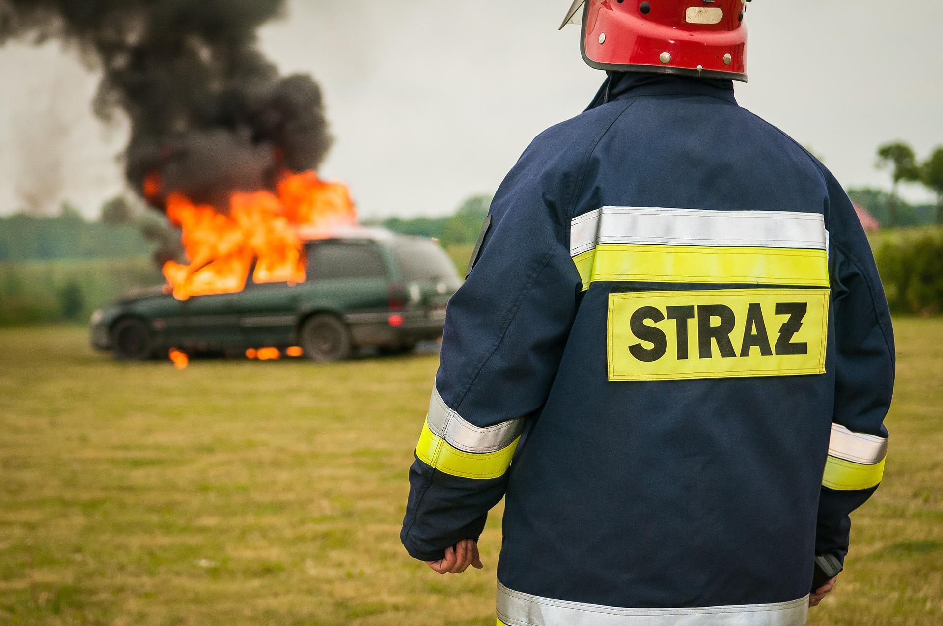 Strażak z płonącym samochodem